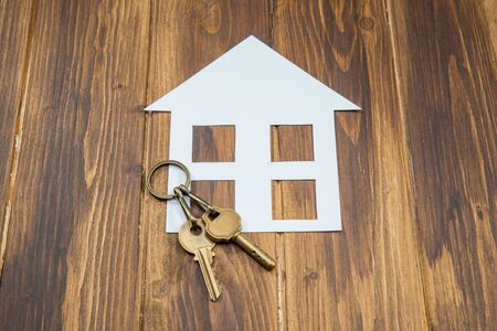company ownership: paper house with key on wooden background