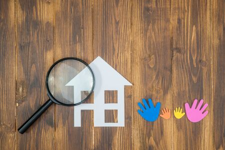inspector kid: family Searching house conceptual, paper house with Magnifier on wooden background Stock Photo