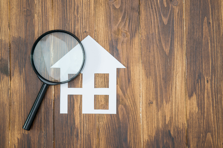 home inspector: paper house with Magnifying Glass, House hunting on wooden background