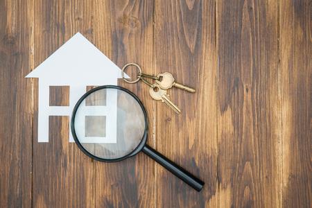 虫眼鏡で家キー、紙、木製の背景での住宅探し 写真素材