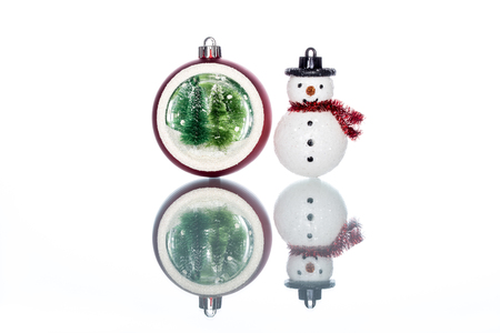 snowglobe with christmas tree inside with snowman on white Background with Reflection