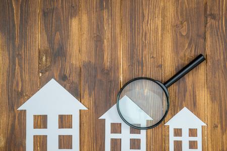 document huis met Vergrootglas, Huizenjacht op houten achtergrond