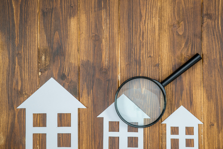 paper house with Magnifying Glass, House hunting on wooden background Imagens - 57030246