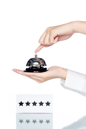 five stars: woman hand holding Service bell with five stars shape card on white background Stock Photo