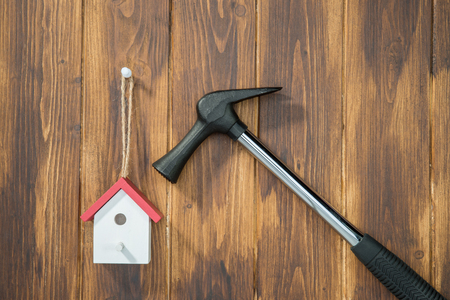 dismantle: Home improvement, model house with Hammer on wooden background
