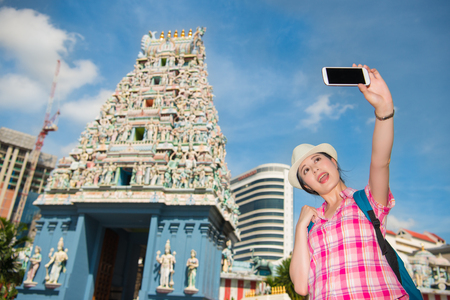 mariamman: Smiling young woman making selfie near Sri Mariamman Temple in Singapore