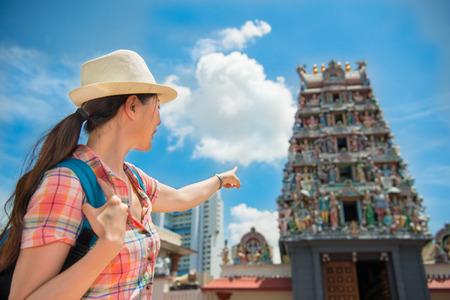 mariamman: Happy Asia woman Travel in Singapore, Pointing Sri Mariamman Temple Stock Photo