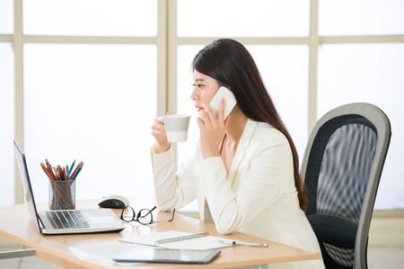 phone professional: Asian attractive businesswoman using smart phone talking and looking at Computer Screen Stock Photo