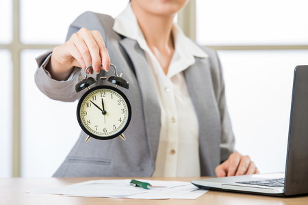corporate waste: Asian businesswoman holding  alarm clock in office