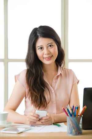 telecommuting: Beautiful young Asian woman using smart phone text messaging at working desk