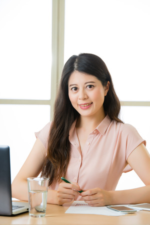 telecommuting: Young Asia businesswoman sitting and smiling at working desk