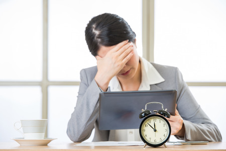 office time: Young asian businesswoman worried about time in office