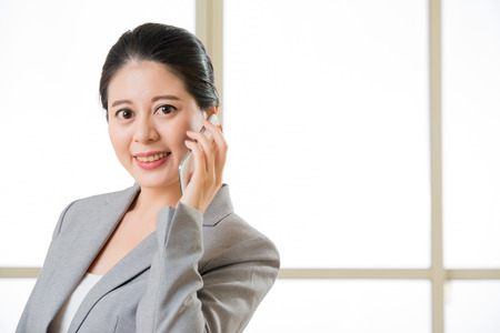 Smiling Business asain Woman talking on a Mobile phone in office