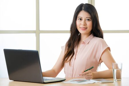 telecommuting: Young Asia businesswoman writing and smiling at working desk