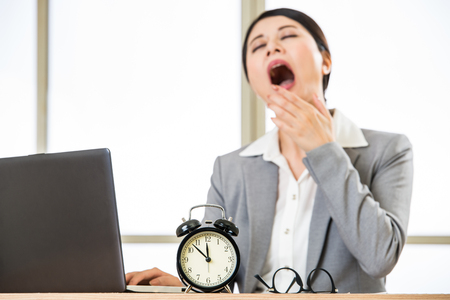 yawing: Tired Asian businesswomen yawing at desk, overtime and overworked