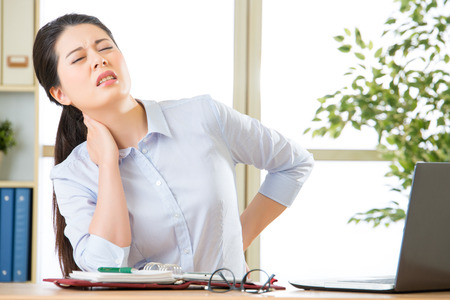 Mujer de negocios asiática joven con dolor en el cuello en la oficina