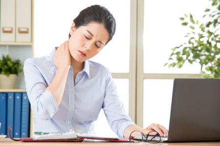 若いアジア ビジネスの女性のオフィスで首の痛みと