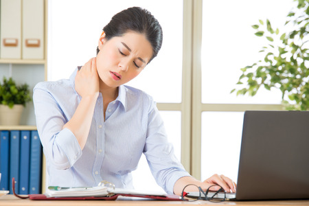 pain: Young asian business woman with pain in neck in office Stock Photo