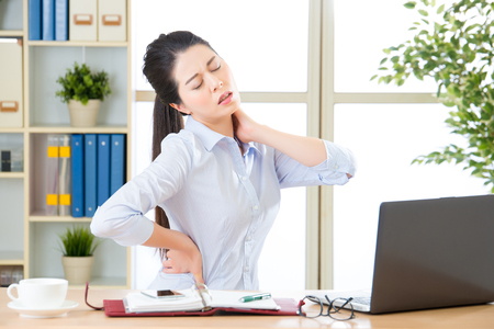 Young asian business woman with pain in neck in office Stockfoto