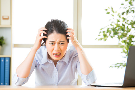 tired person: Young asian business woman overworked with uncomfortable in office