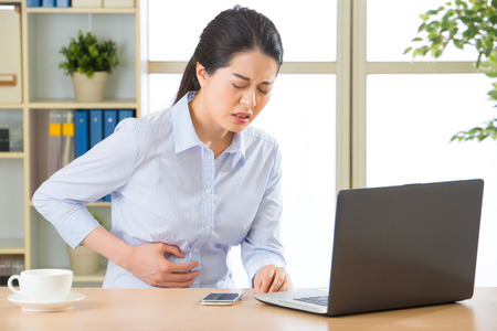 Young asian business woman with stomachache in office Stock Photo