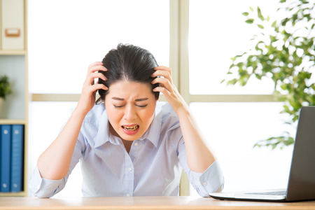 uncomfortable: Young asian business woman overworked with uncomfortable in office