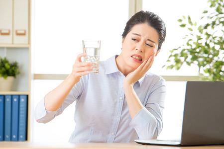 Jeune femme d'affaires asiatique avec la sensibilité des dents dans le bureau