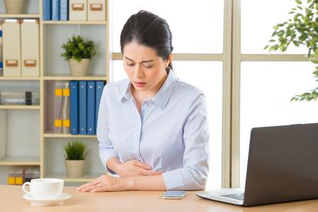 Jeune femme d'affaires asiatique avec stomachache dans le bureau Banque d'images - 59478580