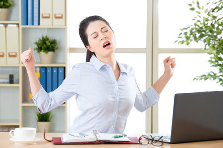 Asian businesswoman fell tired and stretching in office