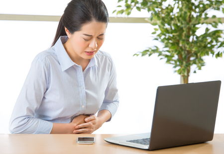 defecation: Young asian business woman with stomachache in office Stock Photo