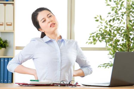 Giovane donna di affari asiatica con il dolore alla schiena in ufficio Archivio Fotografico - 59478615