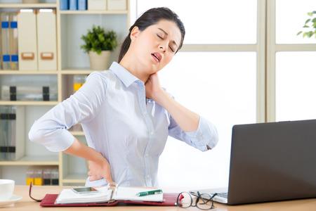 사무실에서 목에 통증을 가진 젊은 아시아 비즈니스 여자