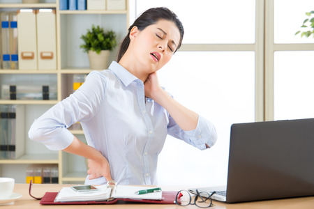 massage chair: Young asian business woman with pain in neck in office Stock Photo