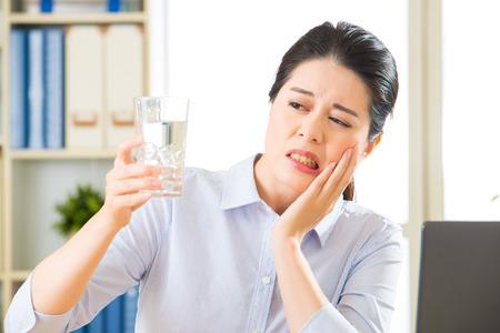 Jeune femme d'affaires asiatique avec la sensibilité des dents dans le bureau Banque d'images - 59478617