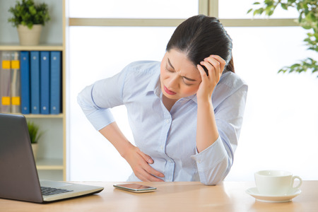 Young asian business woman with stomachache in office Imagens