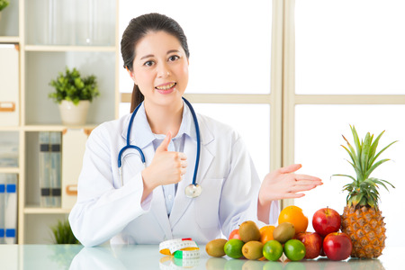 Young asian nutritionist recommend eating fruits and thumbs up, healthy eating