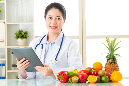 Doctor nutritionist using digital tablet with fruits and vegetable, health eating