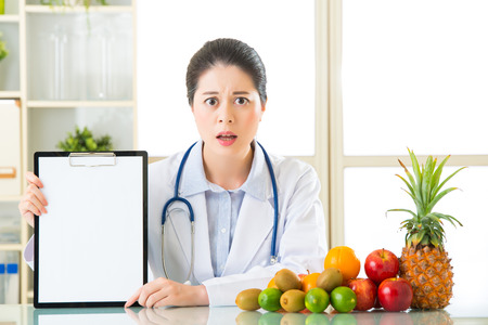 Doctor nutritionist with fruits and holding blank clipboard fell fear, examining report