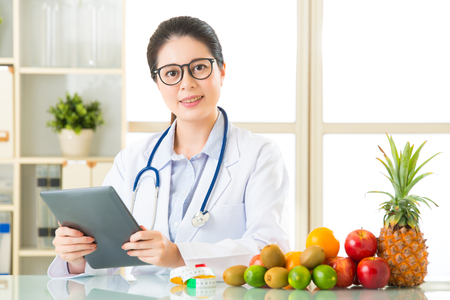 a lady doctor: Young asian nutritionist doctor using digital tablet, diet plan Stock Photo