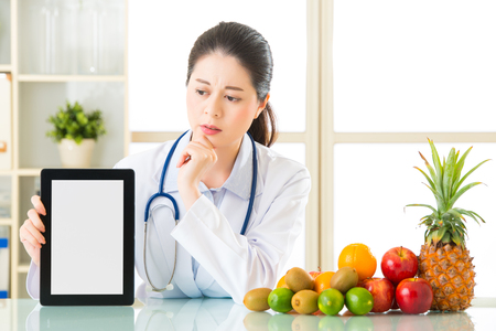 confound: Doctor nutritionist with fruits and holding digital tablet fell doubt, examining report Stock Photo