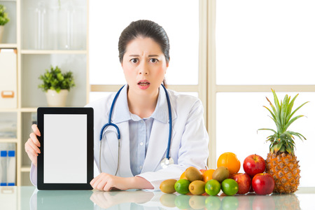 Doctor nutritionist with fruits and holding digital tablet fell fear, examining report