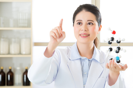 molecular model: asian female scientist doing research on touch screen and holding molecular model