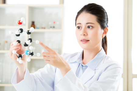 antidote: asian female scientist holding and looking at molecular model doing the Science research for human longevity Antidote