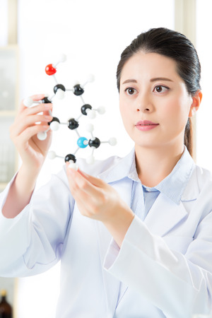 molecular model: asian female scientist holding and looking at molecular model doing the Science research