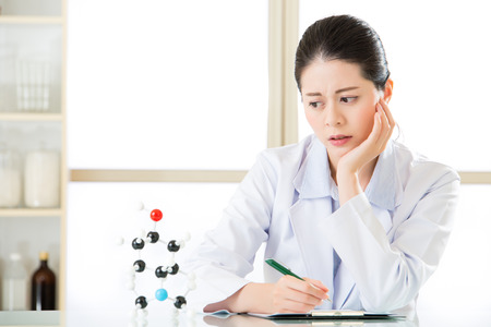 figure out: asian female chemist  try to figure out Chemical formula on clipboard for science research Stock Photo