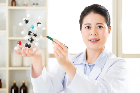 molecular model: asian female scientist teacher point at molecular model explain Scientific wonders with a green pen