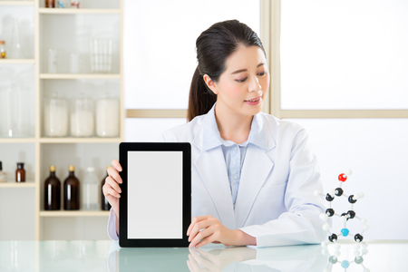 molecular model: asian female chemist use notepad to research for future Chemical formula and holding molecular model
