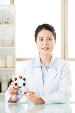 molecular model: asian female scientist Examining the building blocks of life with molecular model in laboratory Stock Photo