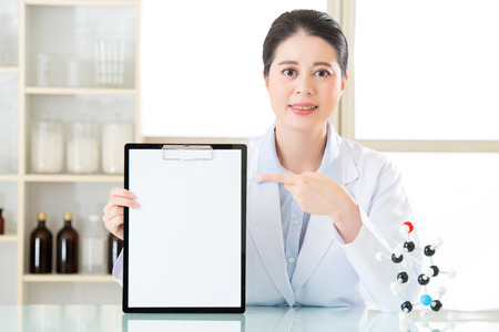 molecular model: Happy asian female scientist holding clipboard and point it with molecular model