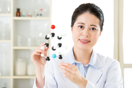 molecular model: asian female scientist holding and looking at molecular model doing the Science research for human longevity Antidote